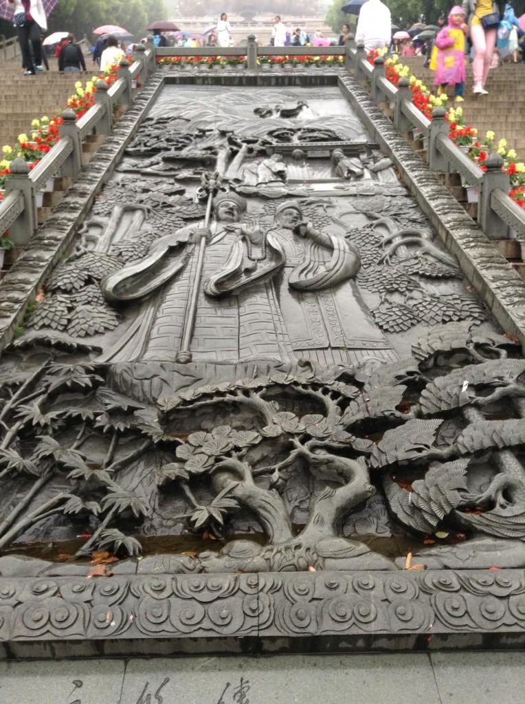 Ukiran di tengah tangga panjang menuju patung besar Buddha